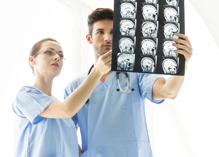 Two doctors looking at MRI scan image of the brain after the brain tumor is removed.